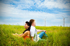 Couple having rest in the meadow. With wind turbines Royalty Free Stock Photography