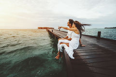 Couple is having romantic date on wooden bridge. Woman in white long dress is showing to her friend something on horizon during beautiful sunset on Maldives Stock Photo