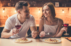 Couple having romantic dinner. Beautiful couple is talking and smiling while having a romantic dinner together in the kitchen Royalty Free Stock Photo