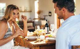 Couple having romantic dinner. Woman smelling the rose given by her boyfriend at dining table. Couple having romantic dinner at home royalty free stock images