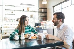 Couple Having Serious Discussion In Cafe. Man and women talking at table while dating in coffee shop stock photos