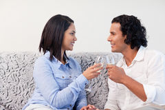 Couple having sparkling wine on the couch Royalty Free Stock Photo