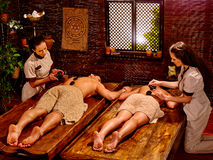 Couple having stone massage. Couple lays her head to window having stone massage. Ayurveda lastone spa treatment royalty free stock photography
