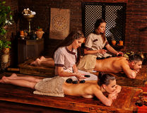 Couple having stone massage. Loving couple having stone massage in indian Ayurveda Spa salon. Man and women lie on the wooden benches decorated with Indian royalty free stock images