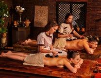 Couple having stone massage. Royalty Free Stock Images