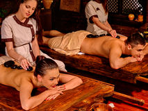 Couple having stone massage. Young family having stone massage. Ayurveda lastone spa massage treatment stock images