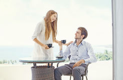 Couple having tea at the balcony. Happy couple hugging and   having tea at the balcony Stock Photo