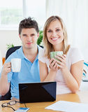 Couple having tea break. After working on a laptop Royalty Free Stock Image