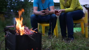 Couple having tea by the fire in the evening stock video footage
