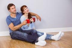 Couple having tea on floor Stock Photo