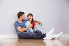 Couple having tea on floor Royalty Free Stock Images