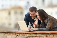 Couple having a video call with a laptop outdoors. With a town in the background royalty free stock photo