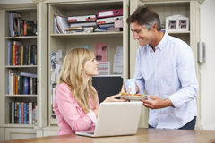 Couple Having Working Lunch In Home Office Together Stock Photos