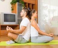 Couple having yoga class Stock Photos