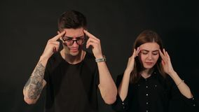 A couple with a headache holding their head. The man and woman with a headache stand on the black background. Portrait of a couple with a headache or problems stock video