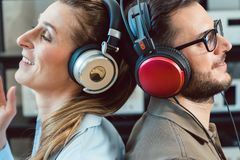 Couple with headphones enjoying music from the Hi-Fi stereo. Leaning at each other stock photos