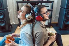 Couple with headphones enjoying music from the Hi-Fi stereo. Leaning at each other royalty free stock image