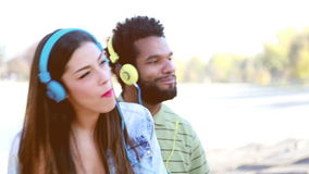 Couple with headphones listening to music and dancing to the rhythm stock video