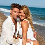Couple with heads together on beach. Royalty Free Stock Photo