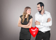 Couple with heart balloon between them in studio Royalty Free Stock Photos