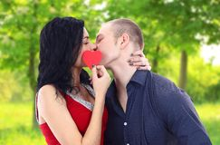 Couple with heart kissing outdoors Royalty Free Stock Photo