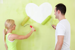 Couple at heart painting on wall Stock Photos