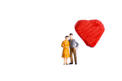 Couple and a heart shape. Couple standing in front of a heart shape on a white background Royalty Free Stock Images