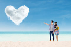 Couple with heart shaped cloud at beach Stock Photo