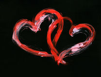Couple of hearts. Two red and white gouache hearts against black background Royalty Free Stock Image