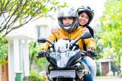 Couple with helmets riding motorcycle Stock Photos