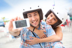 Couple with helmets taking selfie on a scooter Royalty Free Stock Photo