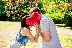 Couple hidding behind a big red heart Royalty Free Stock Photography