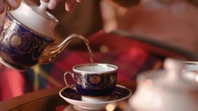 The couple hiding behind a blanket drinking tea and looking photo stock video footage