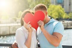 Couple Hiding Behind Heart Shape Stock Image