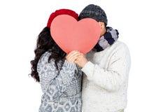 Couple hiding behind heart shape cardboard Stock Photo