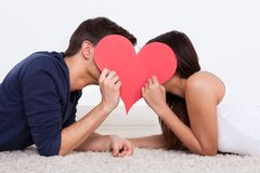 Couple hiding behind heart shape at home. Side view of young couple hiding behind heart shape while lying on rug at home Royalty Free Stock Photography
