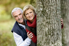 Couple hiding behind tree. Playful couple hiding behind tree Royalty Free Stock Image