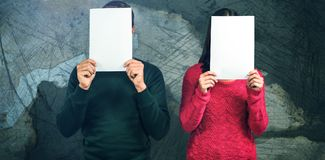 Composite image of couple hiding faces with blank papers. Couple hiding faces with blank papers against rusty weathered wall Stock Images
