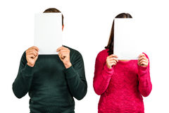 Couple hiding faces with documents. While standing on white background Royalty Free Stock Photos