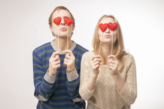 Couple hiding their eyes behind  little red hearts Stock Photos