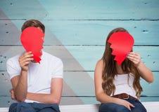Couple hiding their face behind broken heart Stock Photos