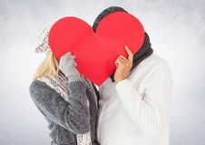 Couple hiding their face behind red heart Royalty Free Stock Photography