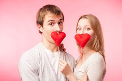 Couple hiding their lips behind  little red hearts Royalty Free Stock Photo