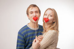 Couple hiding their lips behind  little red hearts Stock Image