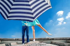 Couple hiding under the beach umbrella on the roof on blue sky. Background Stock Photo