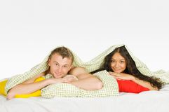 Couple Hiding Under Covers in Bed Royalty Free Stock Images