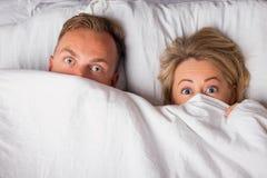 Couple hiding under sheets Stock Photos