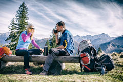 Couple hike and drink in mountains. Man and women hikers hiking and drinking in mountains. Young couple looking at map and planning trip or get lost. Vintage royalty free stock photos