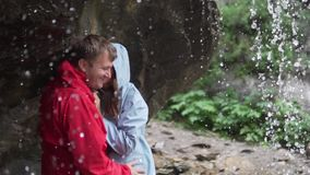 A couple on a hike stands under a stream of a waterfall in non-wet jackets,. Family day. Lovers kiss under a waterfall. A couple on a hike stands under a stream stock video footage