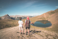 Couple of hiker on the mountain top looking at blue lake and mountain peaks. Summer adventures on the Alps. Wide angle view from a Stock Image